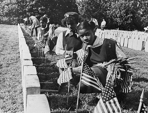 Girl Scouts from Sumter County, Ga. place flags on graves in Andersonville National Cemetery